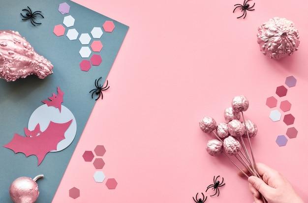 Artisanat de papier créatif halloween à plat sur papier divisé rose et gris avec copie-espace. main tenant la citrouille peinte rose, les chauves-souris et les araignées noires.