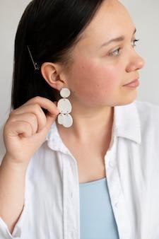 Artisane montrant des boucles d'oreilles faites à la main