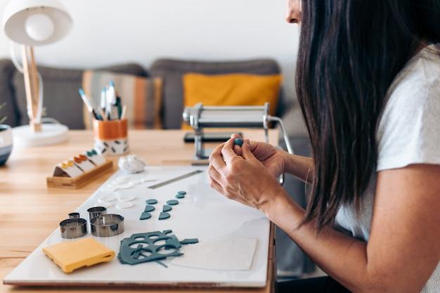 Artisane non reconnue assise à la maison et fabriquant des bijoux faits à la main avec de l'argile.