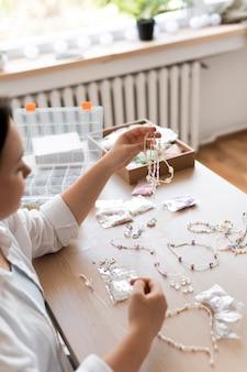 Artisane travaillant avec un collier de perles