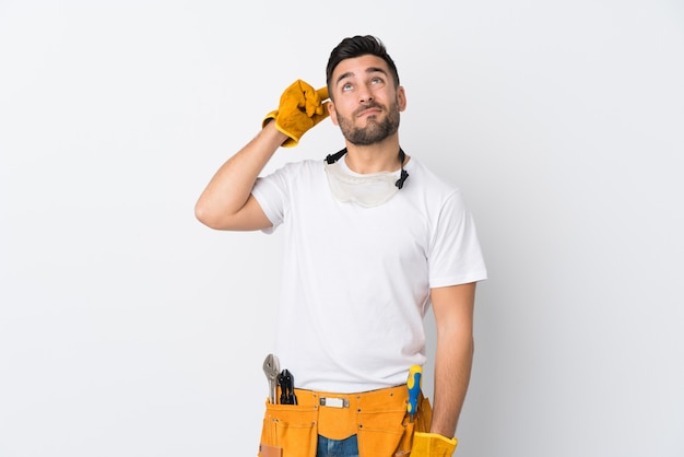 Artisans ou électricien homme sur mur blanc isolé ayant des doutes et avec une expression de visage confuse
