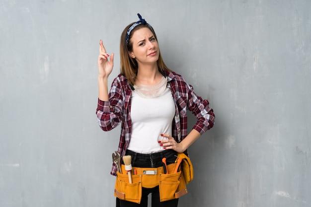 Artisans ou femme électricien avec les doigts qui se croisent et souhaitant le meilleur