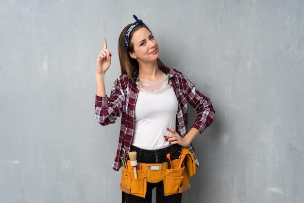 Artisans ou femme électricien montrant et en levant un doigt en signe du meilleur