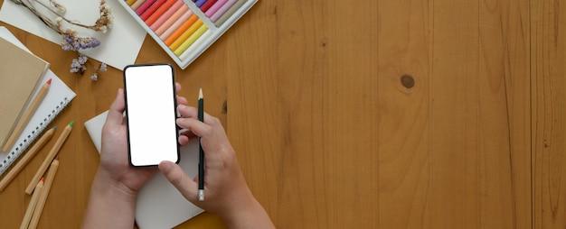Artiste à l'aide d'un smartphone à écran vide tout en travaillant sur une table de travail en bois