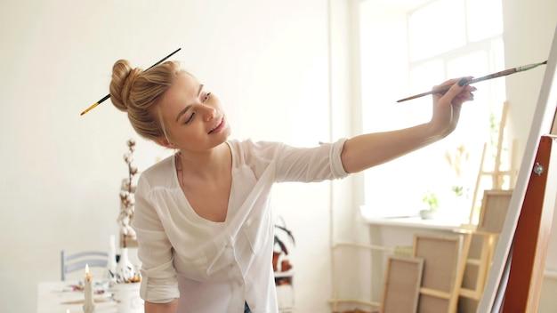 L'artiste attrayant dessine une image sur holt assis. gros plan du processus de peinture dans l'atelier.