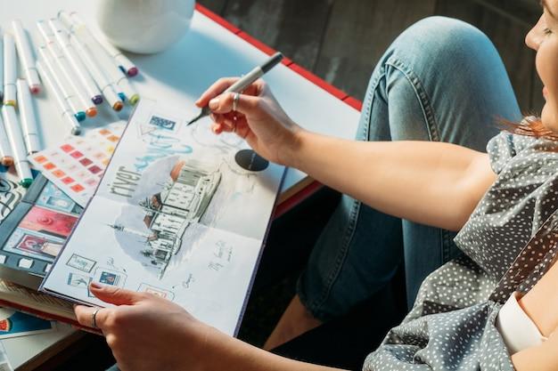 Artiste au travail. contemplation et inspiration. femme avec carnet de croquis et dessin au crayon feutre