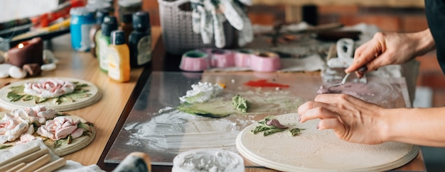 Artiste au travail. lieu de travail de studio. oeuvre en céramique en cours. artisanat. femme avec des outils de modélisation en main.