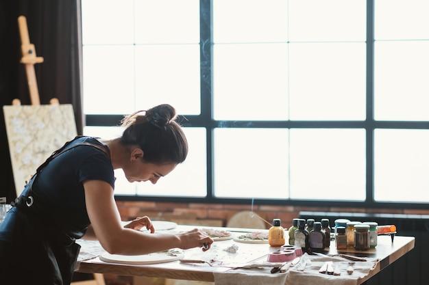 Artiste au travail. lieu de travail de studio. oeuvre en céramique en cours. artisanat. femme avec des outils de modélisation en mains.