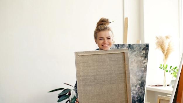 Artiste blonde séduisante heureuse de son travail, l'artiste tient sa peinture dans ses mains