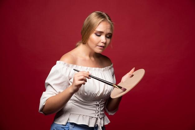 L'artiste blonde tient une palette et des pinceaux et a l'air concentrée et concentrée sur son travail.