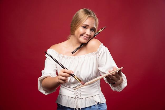 L'artiste blonde tient une palette et des pinceaux et a l'air positive et dévouée.