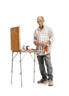 Artiste caucasien masculin, peintre au travail isolé sur fond de studio blanc. peindre, travailler les couleurs, faire de la composition. concept d'occupation professionnelle, travail, emploi, production artisanale.