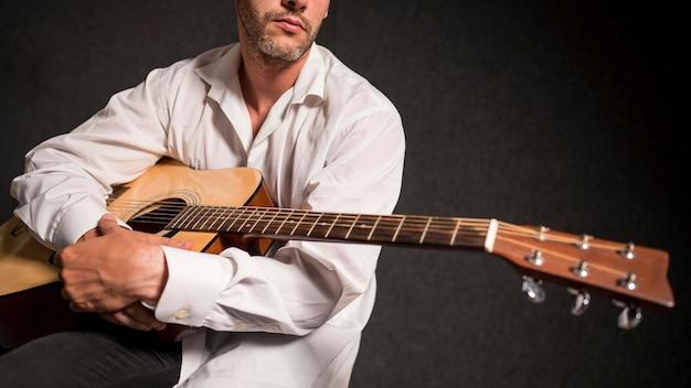 Artiste en chemise blanche tenant sa guitare acoustique