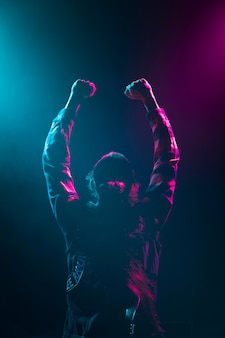 Artiste cheveux longs tenant la main en l'air sur scène
