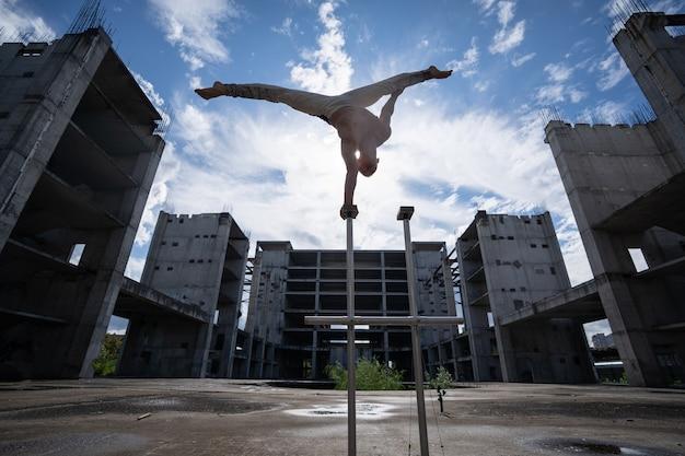 L'artiste de cirque garde l'équilibre d'une part sur le ciel et l'arrière-plan de la construction industrielle