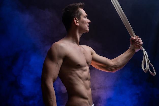 Artiste de cirque masculin musclé avec sangles aériennes sur fond noir et fumé