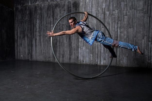 Artiste de cirque musclé dans une roue cyr sur fond noir
