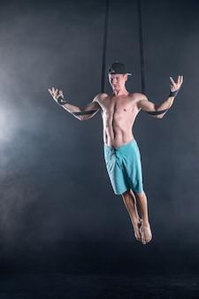 Artiste de cirque sur les sangles aériennes avec des muscles forts sur fond noir portant des vêtements décontractés.
