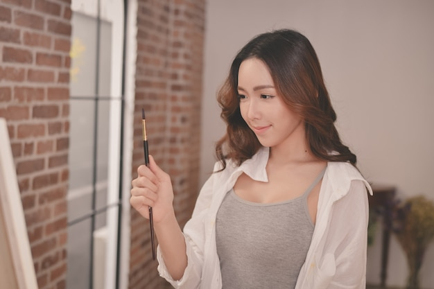 Artiste de concept belle fille. jeune artiste peignant dans la galerie.