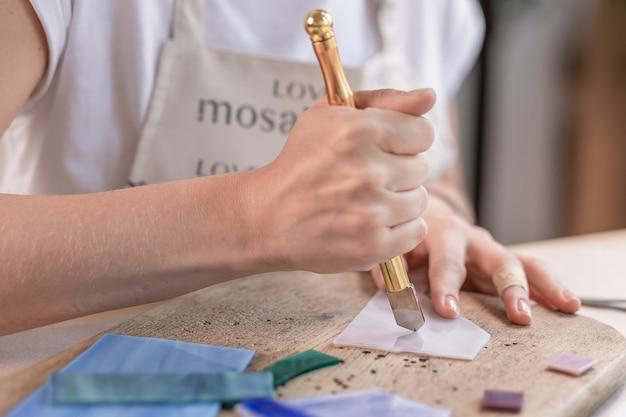 Artiste coupant des feuilles de vitrail en petits carrés de mosaïque. fermer