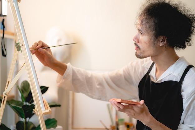 Artiste créatif travaillant sur l'art des couleurs pour dessiner une image avec de la peinture au pinceau dans un passe-temps, atelier d'artisanat d'outils de pinceau aquarelle avec toile en studio, chevalet à palette et arrière-plan de conception d'œuvres d'art