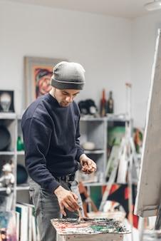 Artiste debout dans un studio confortable et mélange de peintures à l'huile