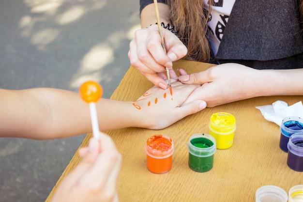 Artiste dessine un motif sur la main de l'enfant