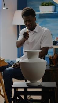 Artiste d'ethnie afro-américaine analysant un vase pour un dessin créatif assis dans un atelier. adulte noir avec imagination artistique utilisant l'inspiration pour un chef-d'œuvre réussi
