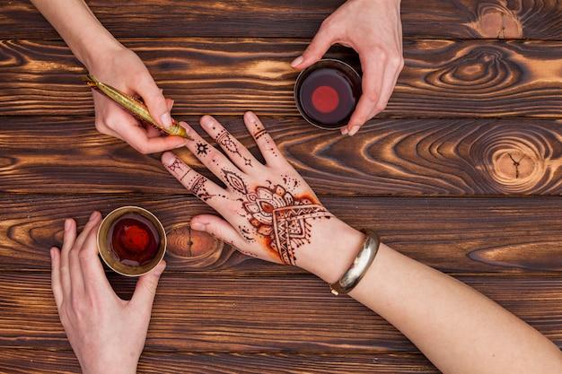 Artiste fabriquant du mehndi sur une main de femme et buvant du thé