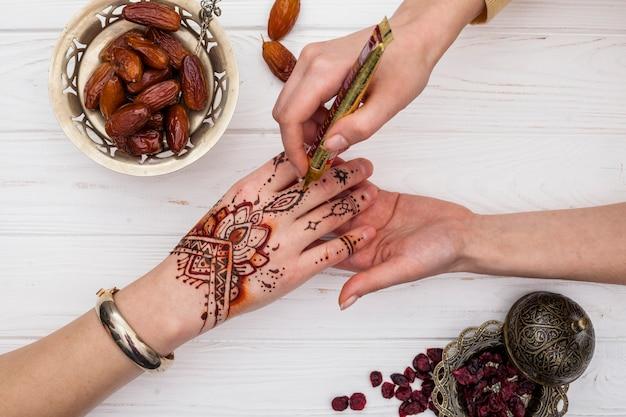 Artiste fabriquant du mehndi sur une main de femme près de fruits secs