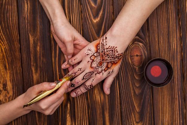 Artiste fabriquant du mehndi sur une main de femme près d'une tasse de thé