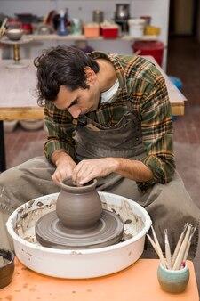 Artiste fabrique de la poterie d'argile sur une roue en atelier