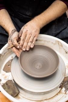 L'artiste fabrique de la poterie d'argile sur une roue de rotation