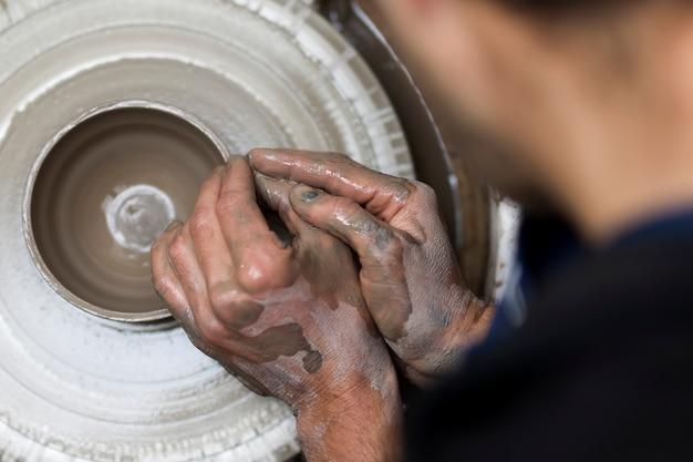 Artiste fabrique de la poterie d'argile sur une roue