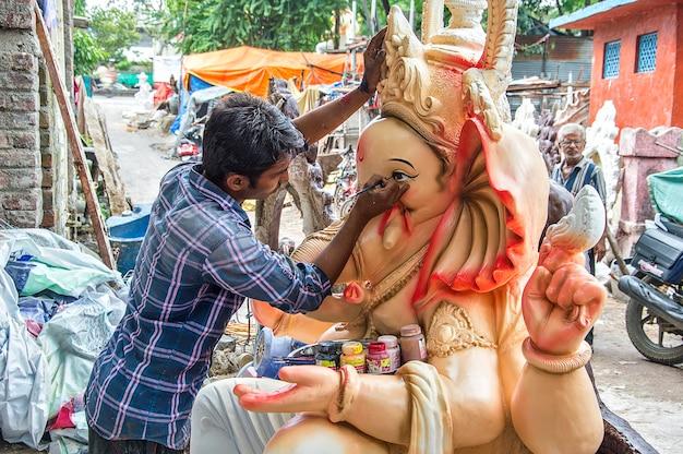 Artiste faisant une statue et donne la touche finale à une idole du dieu hindou lord ganesha dans un atelier d'artiste pour le festival de ganesha.