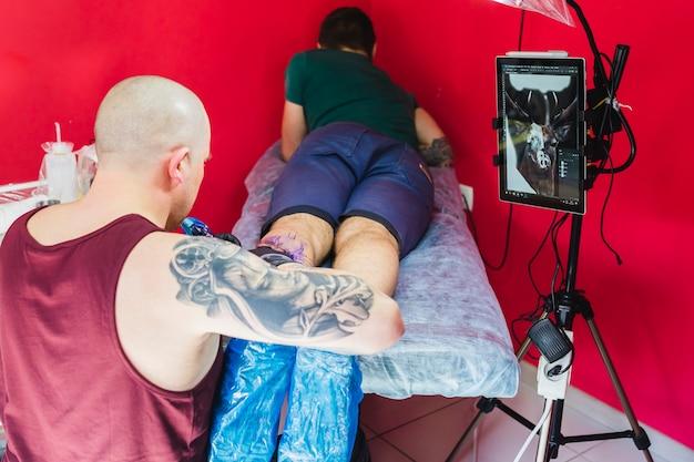 Artiste faisant tatouage sur la jambe dans l'atelier