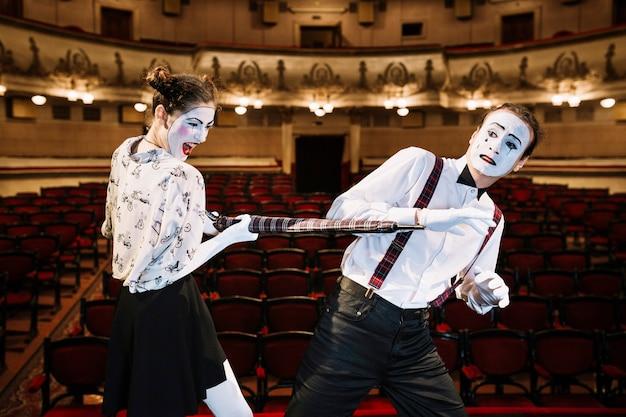 Un artiste féminin mime en colère frappant un mime masculin avec un parapluie dans l'auditorium