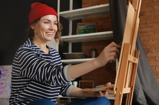 Artiste féminin peignant en atelier