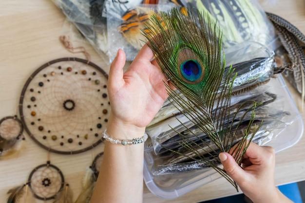 Artiste féminine choisissant une plume de paon naturelle pour créer un capteur de rêves à l'amulette de décoration d'atelier