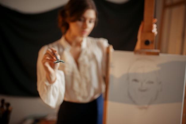 Artiste féminine debout contre chevalet en studio