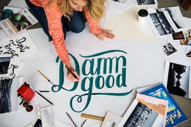 Une artiste féminine écrit le mot sur un papier