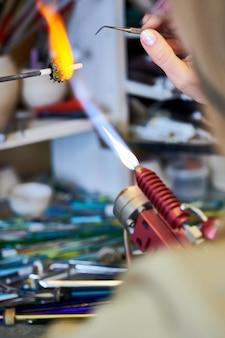 Artiste féminine façonner des perles de verre