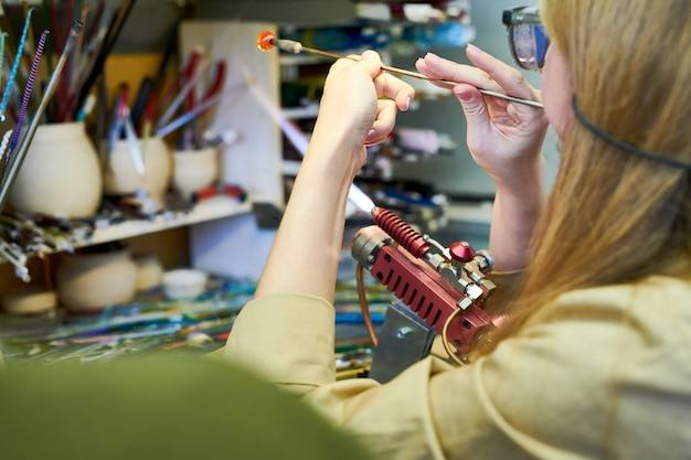 Artiste féminine faisant des perles de verre