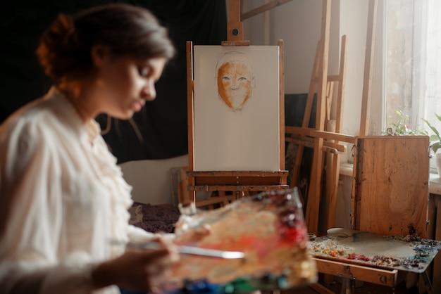 Artiste féminine avec palette de couleurs et pinceau