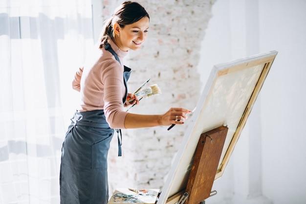 Artiste féminine peignant en studio