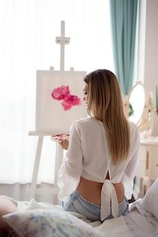 Artiste féminine peint une image sur toile avec des peintures à l'huile à la maison, vue arrière.