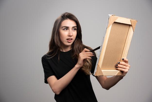 Artiste féminine peinture sur cadre photo.