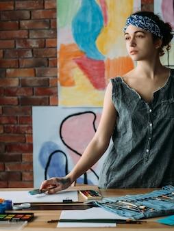 Artiste féminine peinture dans un espace de travail créatif