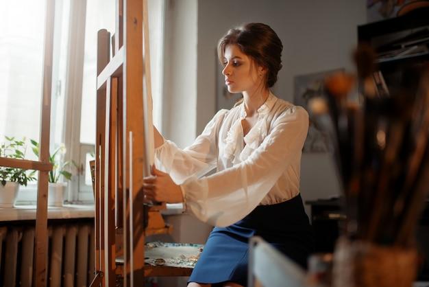 Artiste féminine travaille au chevalet en studio