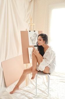Artiste de femme asiatique pleine longueur en chemise blanche, buvant du café tout en dessinant avec un crayon (concept de mode de vie femme)